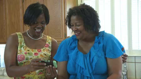 africký : Three lovely African American women working in a kitchen share a moment of laughter inspired by what they see on a smart phone.