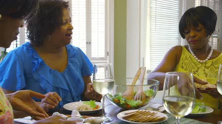 ailelerin : Three pretty African American ladies pass around the lunch dishes during a little family luncheon.