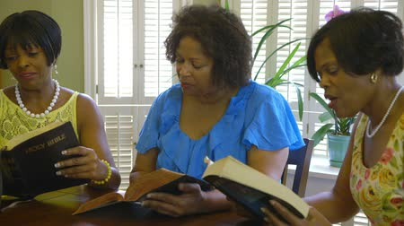 Библия : Three lovely African American ladies engage in conversation during Bible study time. Wide shot.