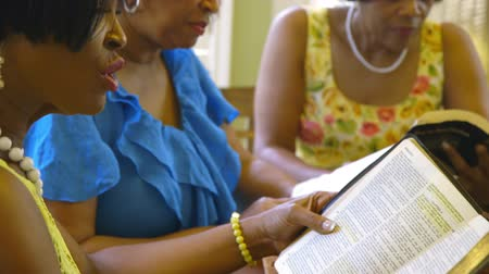 leitor : Focus moves from a women listening and nodding with approval to her friend who is reading from the Holy Bible.