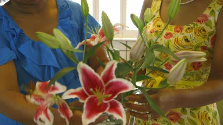 kokulu : Two lovely African American friends or sisters using lilies as part of their flower arrangement.