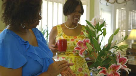 веселье : A lovely African American woman is encouraged by her friend as she works on a flower arrangement for her home.