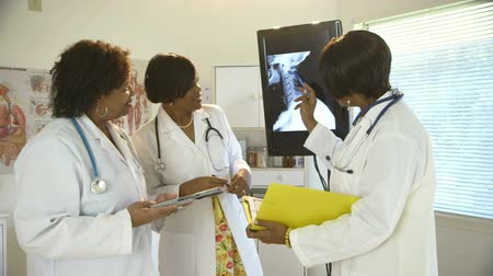 discutir : Three African American physicians in a clinic discuss the x-ray displayed on a large monitor. Vídeos