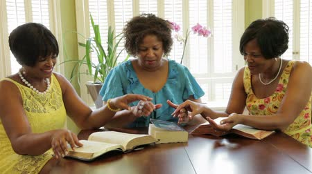 Библия : Finished with their home Bible study time three lovely ladies join hands in prayer. Стоковые видеозаписи