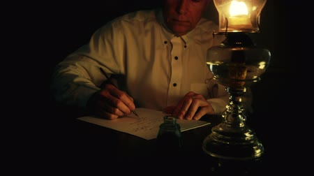 lampa naftowa : A man lit from the light of an oil lamp dips his pen in an inkwell and begins writing on a piece of paper.
