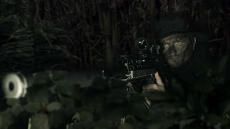 mise : Soldier trained as a sniper surrounded by darkness takes aim with his weapon.