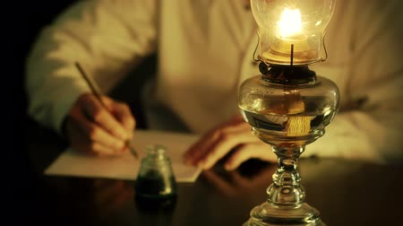 lampa naftowa : A man lit from the light of an oil lamp dips his pen in an inkwell and begins writing a letter. Focus is on oil lamp.