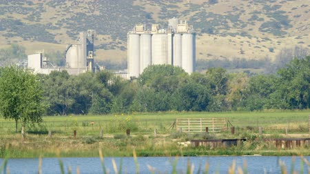 pedregulho : A grain processing plant with a lovely lake in front of it and Colorado mountains in the distance. Stock Footage