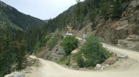 enrolamento : Cars driving up Old Fall River Road near Estes Park Colorado which is a winding one way dirt mountain road.