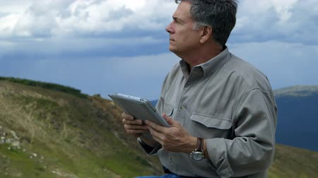 wilds : A man sitting in a desolate mountainous region is able to use his electronic tablet to get information about his surroundings.