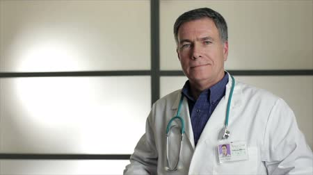 fogadtatás : A doctor standing in front of large opaque wall panels puts a stethoscope around his neck then crosses his arms and smile for the camera.