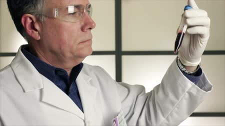 пробирка : A laboratory technician or chemist looks at a sample in a special capped vial he is holding.