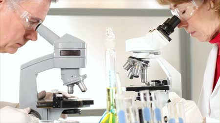 deneyimli : Mature scientists or chemists in a laboratory setting using microscopes in their research.