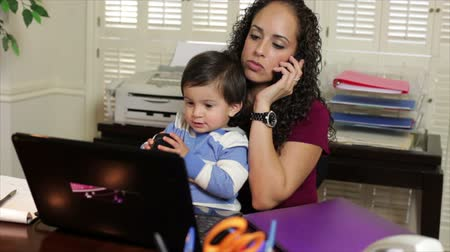 annelik : A pretty Hispanic work at home mom holds her son while taking a phone call in order to conduct business.