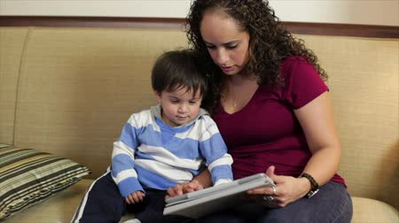 öğretim : A cute little Hispanic toddler captivated by he sees on the electronic tablet his mother is holding. Stok Video