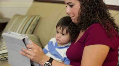 educacional : A pretty Hispanic mom uses an electronic tablet as an entertaining and educational tool for her little son.