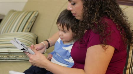 watching : An adorable little Hispanic toddler is captivated by what his mother is showing him on an electronic tablet.