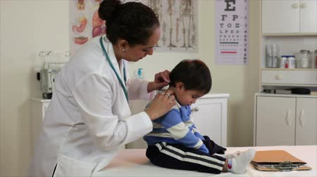 хорошее здоровье : A pretty Hispanic pediatrician examines a cute little toddler who appears entertained with something on the exam table. Стоковые видеозаписи