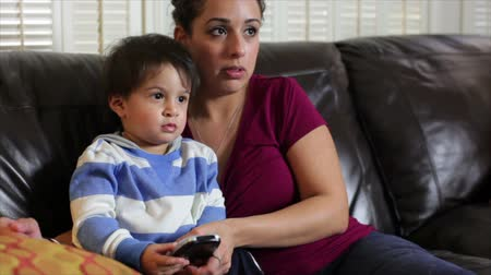 ailelerin : A pretty Latina sits on the couch with her toddler and uses the remote control to change TV channels.