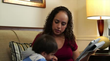 zajímavý : A pretty Hispanic mom using an electronic or digital tablet during playtime with her cute little son. Dostupné videozáznamy