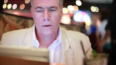 освещенный : Businessman sitting in a colorfully lit restaurant or bar using an electronic tablet enjoys a drink.
