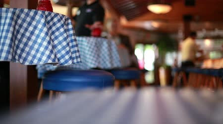 ресторан : View of restaurant activity from the top of a blue checkered tablecloth covered table.