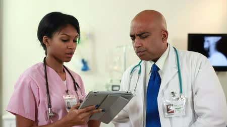 asian and indian ethnicities : Camera tilts up to a pretty African American nurse and an Indian doctor going over what they see on an electronic tablet. Stock Footage