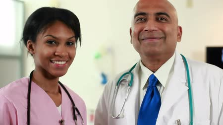 egészségügy és az orvostudomány : Indian physician and pretty African American nurse stop talking and smile for camera. Camera dolly shot. Stock mozgókép