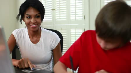 özel öğretmen : A pretty African American tutoring a boy smiles at him as he works diligently.