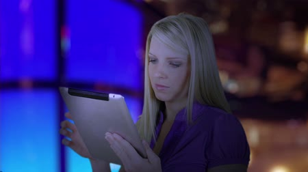 еще : Light from her electronic tablet lights the face of a pretty woman standing in a dimly yet colorfully lit room.