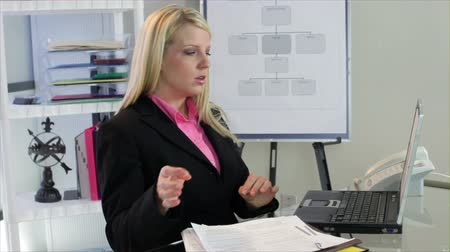 woman working : A lovely blond businesswoman who appears stressed out about something that is giving her a tension headache. Stock Footage