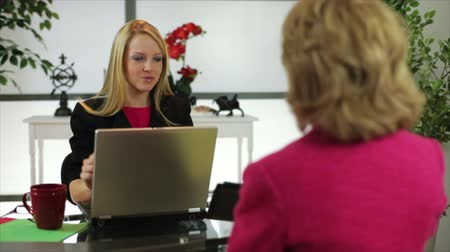 discutir : A pretty blond woman sitting in her office greets another who shakes her hand and sits down.