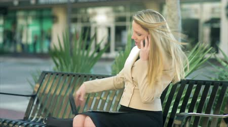 деловая женщина : A pretty businesswoman finishes her cell phone call as she sits down on a sidewalk bench and starts using an electronic tablet.