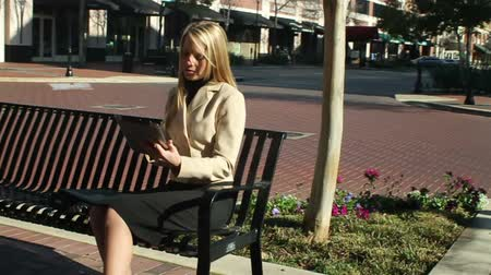 деловая женщина : Slow motion steadicam shot of a businesswoman sitting on a sidewalk bench using a digital tablet.