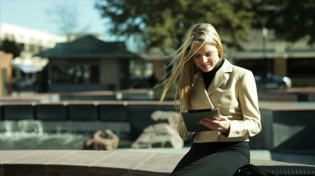 ona : A pretty blond businesswoman sitting by of a city fountain using her digital or electronic tablet smiles at what she sees.