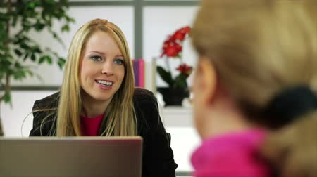 discutir : An enthusiastic girl sitting in her office engages in lively conversation with a woman sitting across from her.