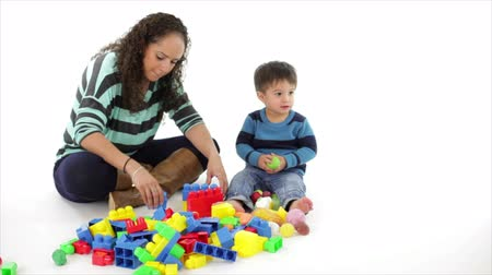 watching : A pretty Hispanic mother and her cute toddler playing with colorful blocks on white background. Stock Footage