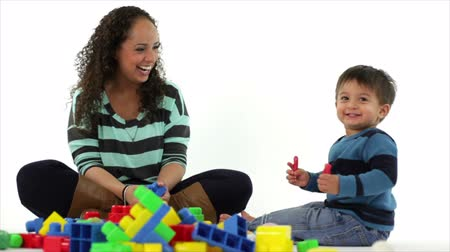 educacional : A lovely amused Hispanic mother and her little son smiling and having fun playing with blocks. White background Vídeos