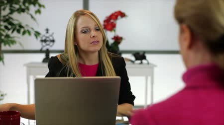 reunião : A friendly greeting and a handshake starts a business meeting in the office of a pretty blond businesswoman.