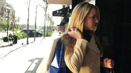 ügy : Camera moves from close up to full body of a lovely blond woman in business attire who is out shopping. Stock mozgókép