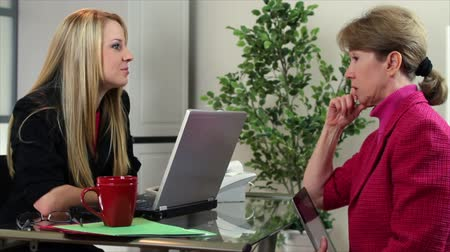 discutir : An enthusiastic girl sitting in an office talks with a mature coworker who hands her an electronic tablet at the end.