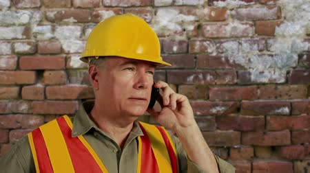 deneyimli : Man in hardhat with old brick wall in background engaged in cell phone conversation. Stok Video