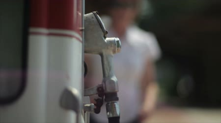 pompki : An out of focus woman walks by the handle of an old service station gasoline pump.