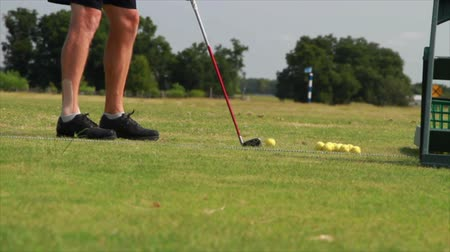 trawa : A male golfer with a piece of tape on his ankle to reinforce it practices hitting golf balls.