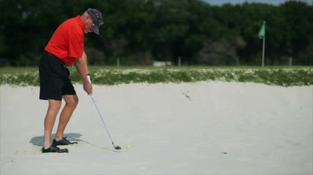 тройник : A male golfer hits a golf ball out of a sand trap on to a green.