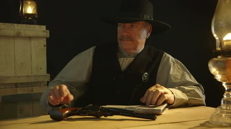 lawman : A cowboy from the American wild west era lowers the newspaper he is reading to reveal a sheriff badge then gets up and leaves with an aggravated expression.