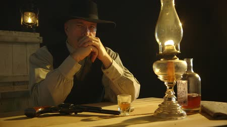 lampa naftowa : A mature pensive cowboy from the American wild west era sitting with booze and pistol contemplates trouble.