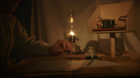 lampa naftowa : A telegrapher from the old American west era in a in a dimly lit tent sends a telegraph message.