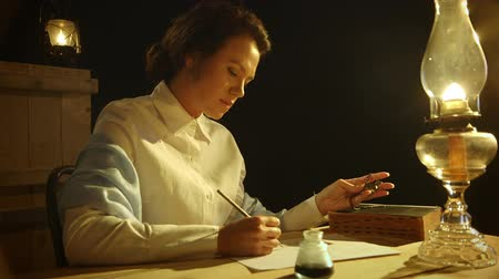 yazarak : A lovely lady from the early American west in a rustic setting writes a letter by lamp light using a dip pen.