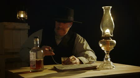lampa naftowa : In a room lit by an oil lamp a cowboy from the American wild west era checks the time on his pocket watch as if waiting for someone to arrive. Wideo